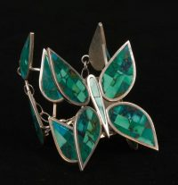 Silver and inlaid turquoise bracelet in the shape of a butterfly with flanking inlaid petal pieces and chain closure by Colin Coonsis, Zuni.